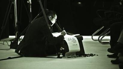 :台前的抄经和幕后的吹奏相得益彰.图片来源:新闻晨报-窦唯在上