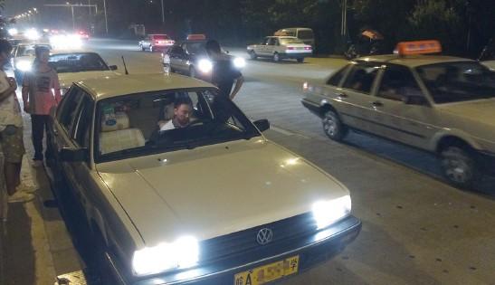 教练车云集在此,五六百人忙着在昏暗的灯光下练习路考项目.高清图片