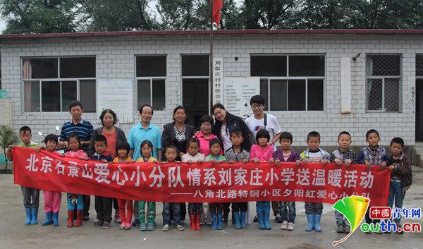 爱心小分队的代表与刘家庄小学老师,同学合影.中青网发 郝克昌 摄图片