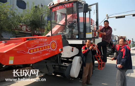 朱涛/村民高高兴兴地将玉米收获机开回家。朱涛摄