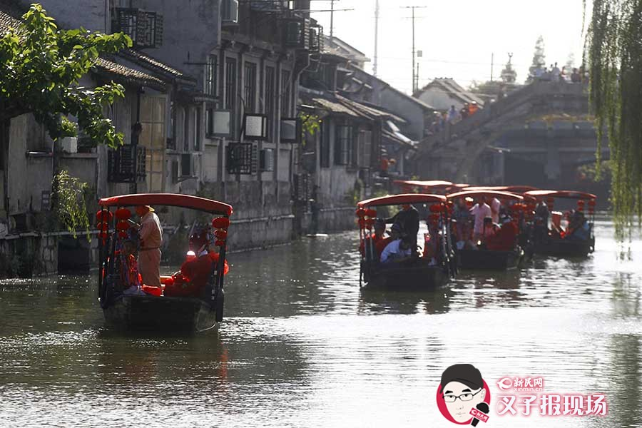 昨天(9月21日),枫泾古镇的小河上,一溜的小船一字排开游玩古镇,船上是一对对参加集体婚礼的新人,而这些新人有些特殊,起码有一方是外籍人士。新民网 图