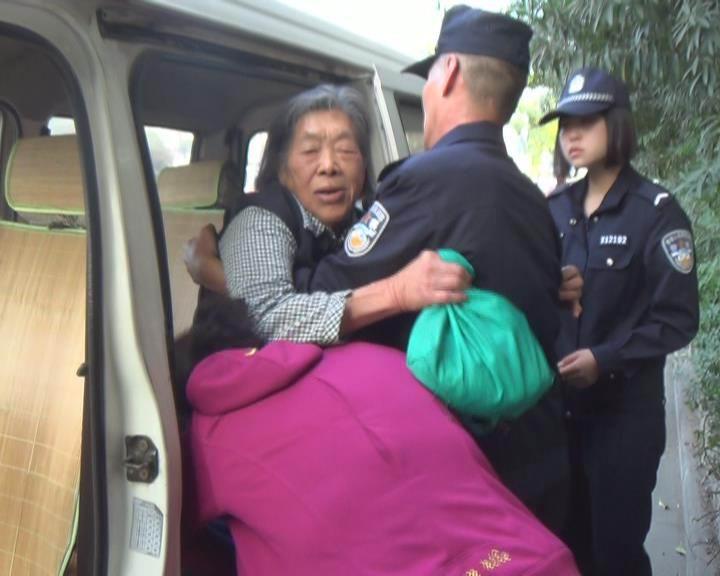 扬州/图为民警将老太抱上车送医院检查治疗。久建摄