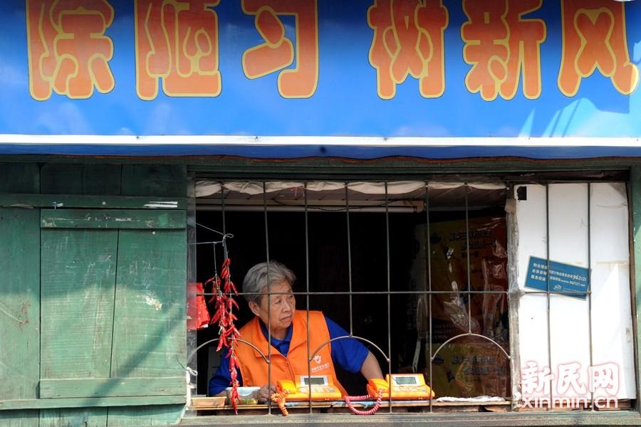 """贺阿婆的电话亭还担当着平安志愿者服务的公益元素,弄口经过的偷盗嫌疑人也离不开阿婆的""""火眼金睛""""。新民晚报通讯员 杨建正 摄"""