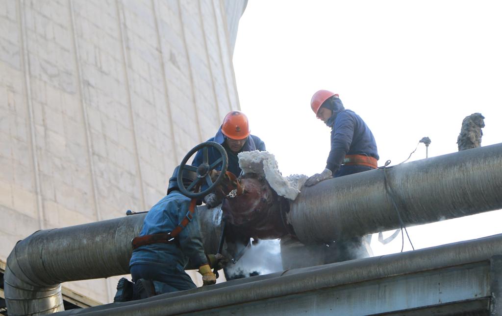 图为公司检修人员正在抢修供热管道的阀门图片