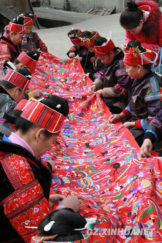 台江县老屯乡苗族刺绣合作社的苗家妇女们围着一块10余米长的壁挂飞图片