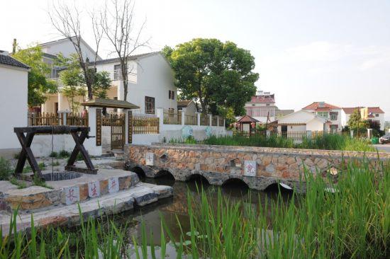 穿越整个村庄,河边的农家小院黑瓦白墙,石头垒起花台,一棵棵盘根错节