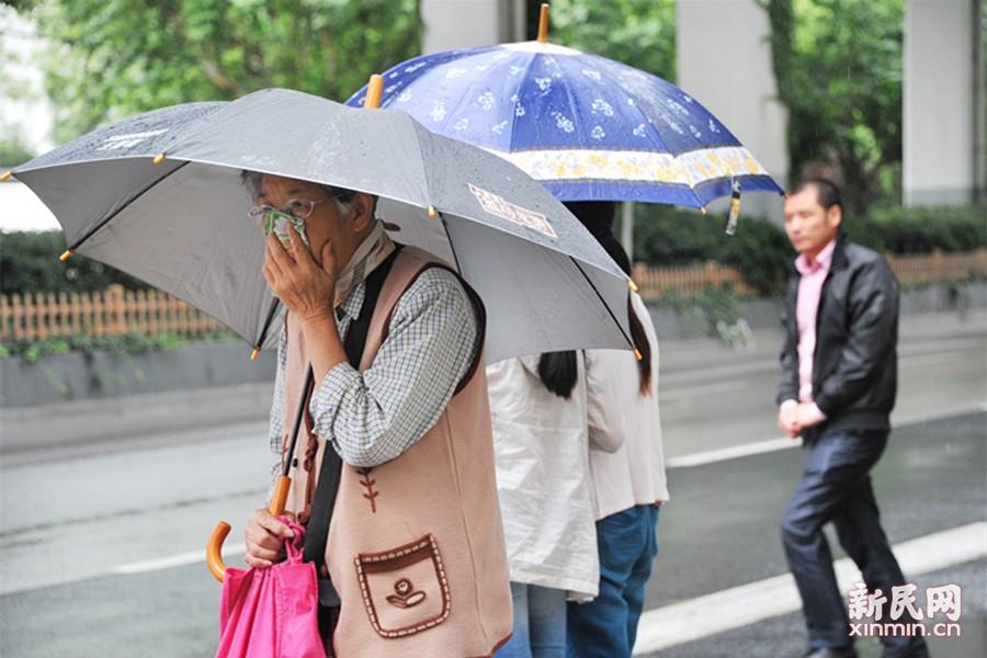 """今天是二十四节气中的""""小暑"""",通常标志盛夏登场,往往会有连续高温天气出现。而就在昨天,申城18.9℃的日平均气温,创下自1873年有气象历史记录以来7月里的历史新低,成为该月的""""史上最冷一天"""",让人直呼看不懂。图为街头一些老年人甚至穿上羊毛背心御寒。新民晚报通讯员 杨建正 摄"""