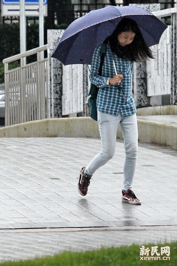 """盛夏7月出现如此""""低温""""是否异常?专家称,此类天气一是与梅雨带、东北冷涡等天气系统的位置、强度、配置有关,另外一方面与上海目前正处在初夏梅雨期中而未进入盛夏的气候背景有关。图为风雨中路人穿着长袖长裤。新民晚报特约通讯员 庄毅 摄"""