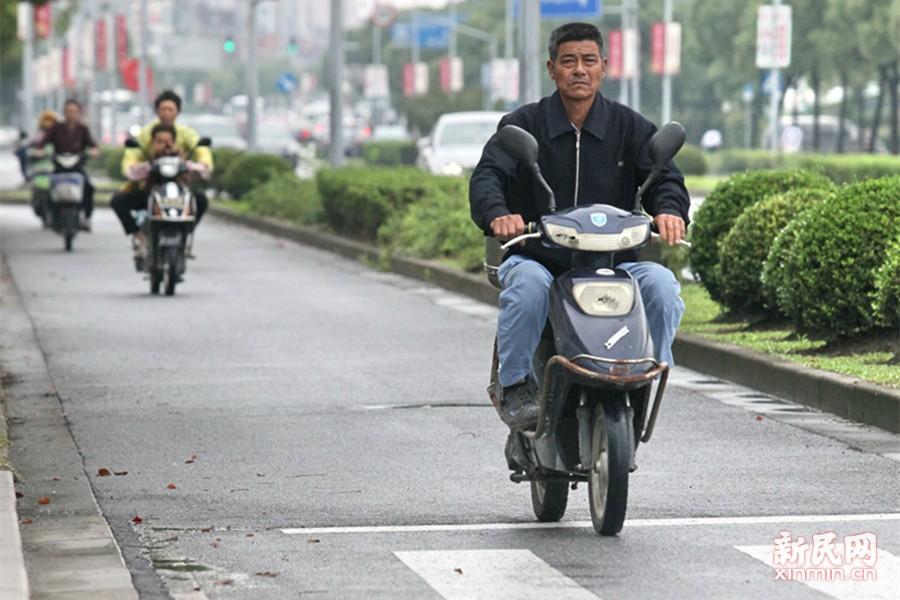 """据上海中心气象台预报,明天气温继续""""低迷"""",但9日起气温会有小幅回升,10日气温就会升至30℃。图为今天上午,在上海金山蒙山北路上,骑电动车的市民穿着较厚实的外套。新民晚报特约通讯员 庄毅 摄"""