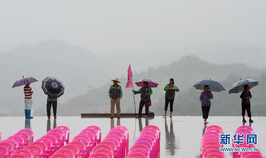 9月1日,在广西南宁市昆仑关,几名市民站在雨中.