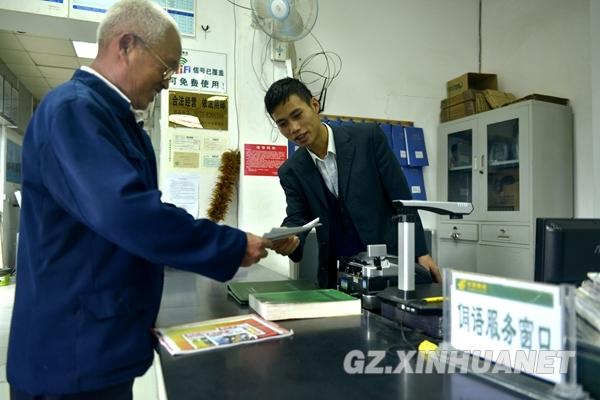 10月9日,一名侗族老人在中国邮政平永邮政支局侗语服务窗口领取报纸.