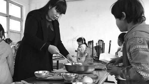 陈晓娅在泗水县苗馆镇东鲸小学给孩子们打饭