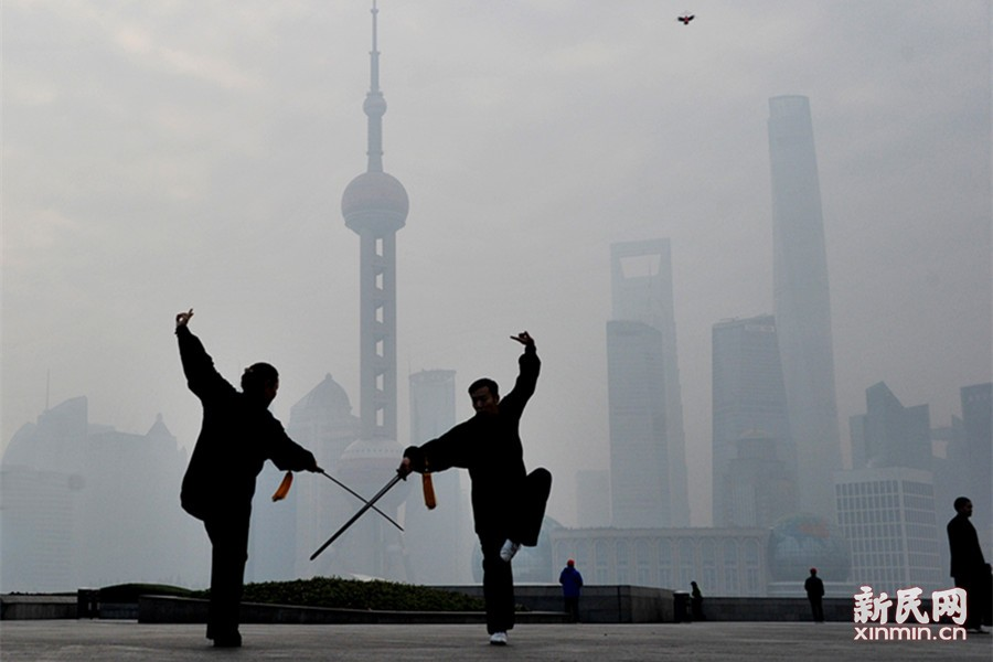 外滩和陆家嘴建筑物在大雾笼罩中时隐时现,晨练的市民在雾中起舞。新民晚报通讯员 杨建正 摄