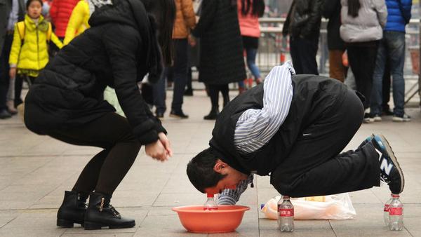 浙江街头一男子跪饮料瓶上乞讨 吸引路人眼球