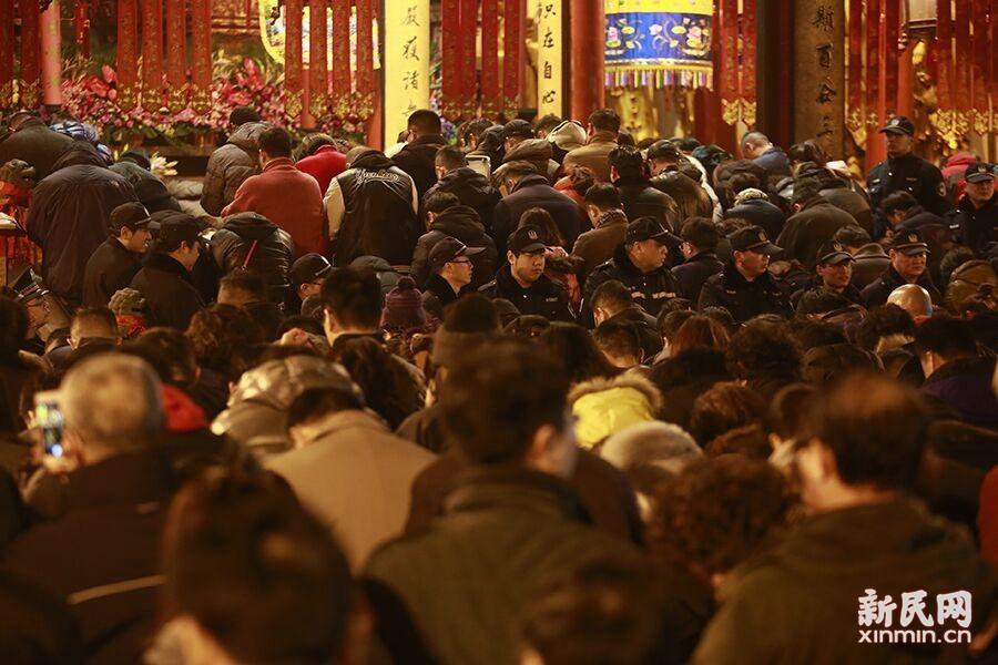 辞旧迎新之际,数千名上海市民来到沪上寺庙,烧头香,撞钟祈福。昨夜9时许,在百年古刹玉佛禅寺已有很多市民排队等候。现场人潮涌动,公安、消防和志愿者齐上阵,保障节日安全。新民晚报新民网 萧君玮 摄