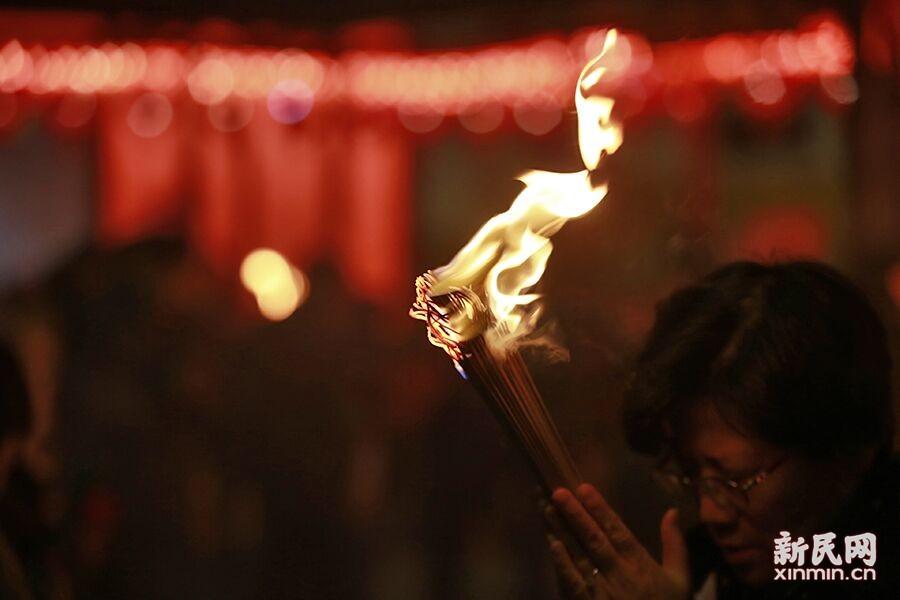 撞钟聆听年钟迎接农历猴年,除夕夜烧头香为新年祈福,是不少上海市民的新年习俗。新民晚报新民网 萧君玮 摄