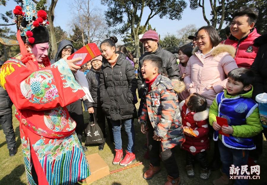 """春节期间,""""百子闹新春""""春节民俗庙会在古猗园精彩上演。新春魔术让孩子大人乐开怀。新民晚报记者 周馨 摄"""