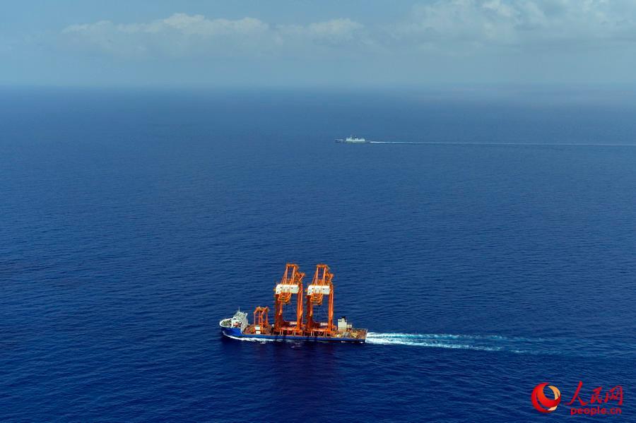 中国籍泛洲9号是一艘重大件运输船,航速稍低于其它被护商船,大庆舰加强对中国籍船舶的护航警戒。彭海摄   人民网亚丁湾3月28日电 当地时间3月28日,海军第二十二批护航编队大庆舰、青岛舰和太湖舰分两个编组护送中外4艘商船,由亚丁湾东部海域开始向曼德海峡附近海域航渡。这是第二十二批护航编队三艘舰艇首次同时为商船护航,也是该编队首次分编组对被护船舶实施护航。   此次护航是中国海军执行的第920批船舶护航任务。27日4时,巴拿马籍海洲9号散货船提前一天抵达会合海域,指挥所决定,青岛舰与其组成第一编组
