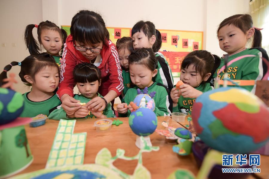 """幼儿园老师朱萍在教小朋友用黏土制作""""心中的地球"""""""