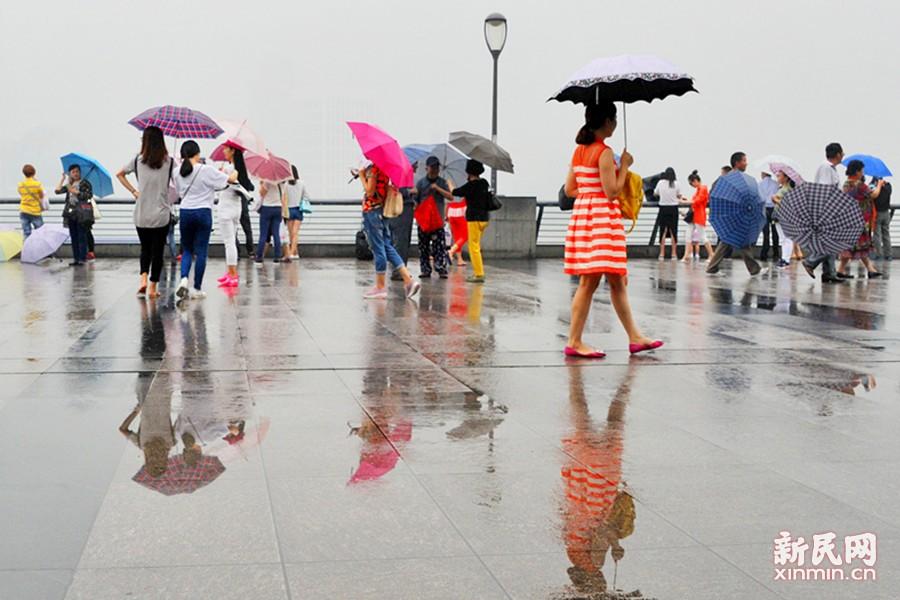 申城从26日起阴雨绵绵,加上温度高、湿度大,似乎进入了黄梅天气。今天,强降水再次来袭,将有大到暴雨。据预报,未来数日,雨水仍将唱主角。图为外滩浦江对岸的建筑物全都朦朦胧胧,时隐时现,游客们打着伞在烟雨朦胧中赏景。新民晚报通讯员 杨建正 摄