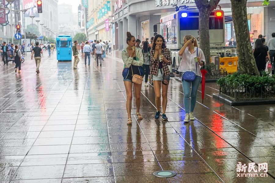 """图为南京东路步行街潮湿闷热,""""老外""""边吃冰激凌边逛街。新民晚报 陈梦泽 摄"""