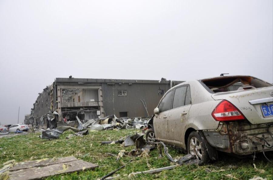 这是6月23日在江苏省阜宁县开发区一电子科技公司拍摄的受灾现场,厂房被掀开,车辆被损坏。新华社发
