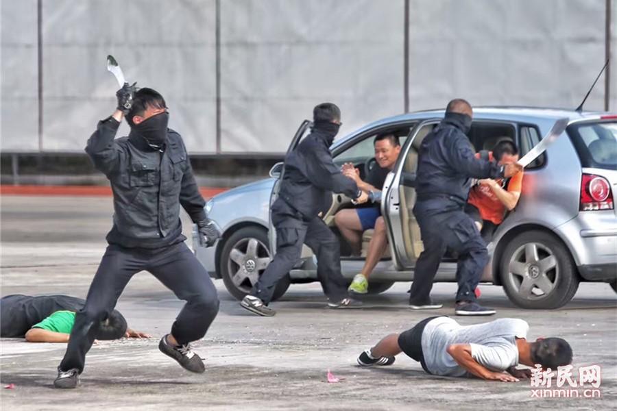 演习最后模拟了3名恐怖分子在广场人流密集区持刀砍杀群众,现场执勤特种机动队员接报后立即开枪击毙1人,另2人抢夺机动车逃跑,1辆执勤车尾随追赶,另1辆设置路障拦截。新民晚报记者 张龙摄