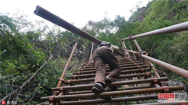 凉山悬崖村绝壁修路 村民背1500根钢管造天梯