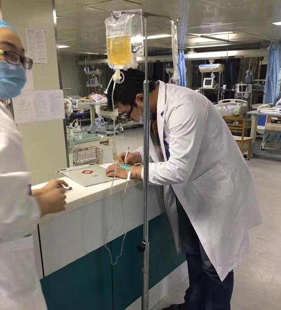 男医生侧脸照片_照片中,一位带黑框眼镜的男医生穿着白大褂,戴着口罩,正在为病人写