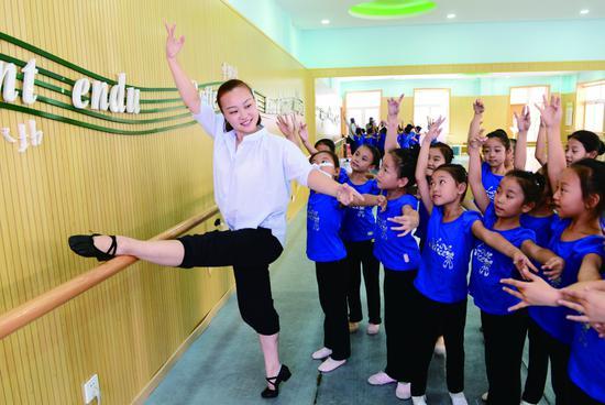 老师教学生舞蹈基本功。摄/本报记者 云凯杰