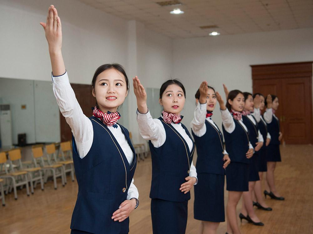 工程系空中乘务专业大一年级的学生们在忙碌地接受严格的专业形体训练