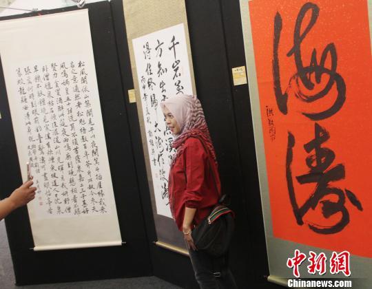 图为印尼青年在中国书法作品前留影。 林永传 摄
