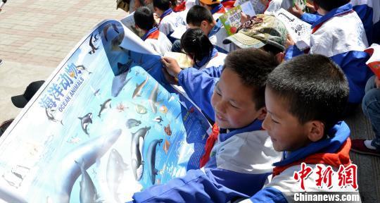 图为学生们拿到彩虹口袋后,查看绘画彩页。 西宁公益联盟 摄