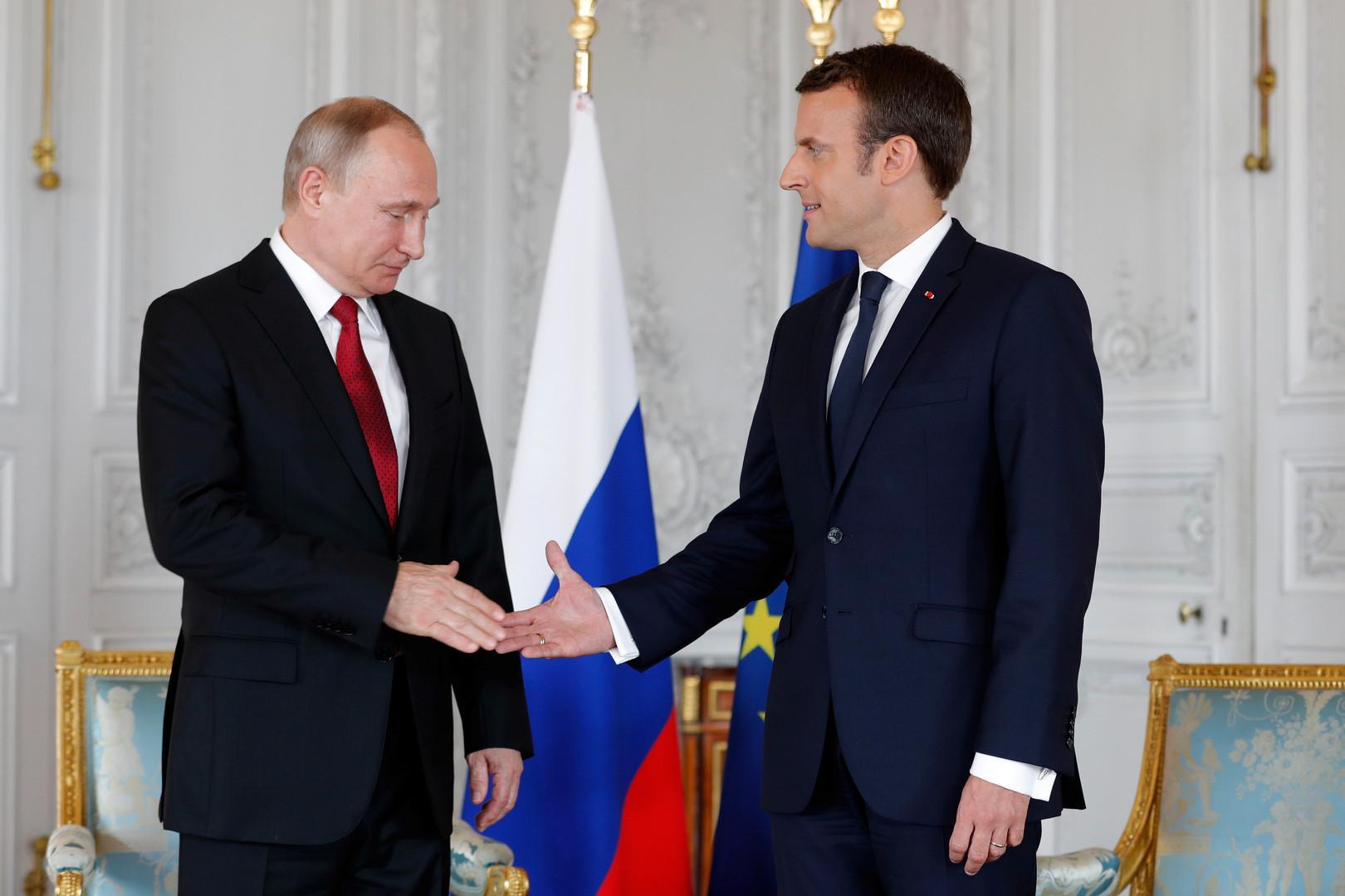 握手瞬间,马克龙直视普京的面孔,后者却盯着马克龙年轻的,戴戒指的图片