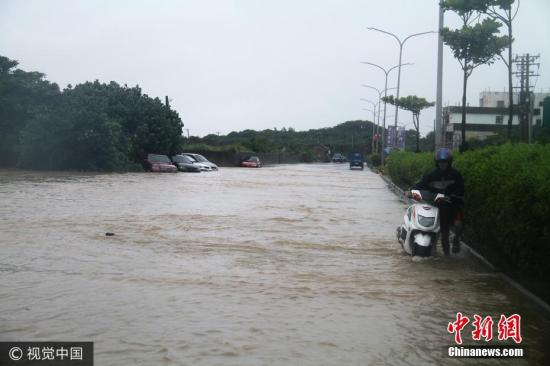 资料图:台湾暴雨来袭,骑摩托车者推车前行。图片来源: