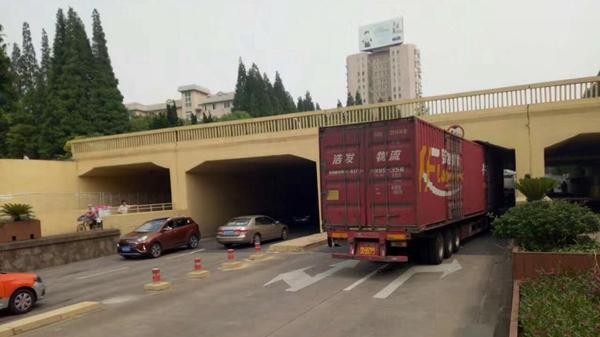 沪金山区一集卡因超高卡在立交桥下 交警对轮胎放气助其脱困