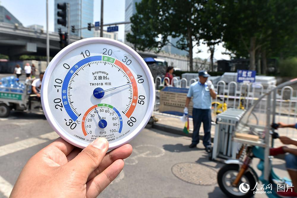 7月11日11点,北京CBD,交通协管员正在疏导交通。此时,烈日下的气温已超过40摄氏度,地表温度接近50摄氏度。(人民网记者 翁奇羽 摄)