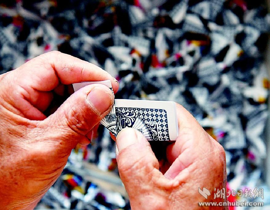 图为一张扑克折成一个插子。潜江市龙湾<a href='http://search.xinmin.cn/?q=柴埠' target='_blank' class='keywordsSearch'>柴埠</a>六组张克华今年65岁,用扑克折花瓶是近年的事。花瓶编制前要构图,接着折插子,插子就像房子的砖瓦,一张扑克折成一个插子,折成足够的插子后开始组装花瓶。(<a href='http://search.xinmin.cn/?q=视界网' target='_blank' class='keywordsSearch'>视界网</a> 吴燕军 金必祥 摄)